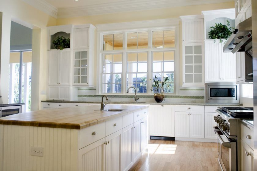 white-wooden-kirchen-cabinets-bright-marble-countertop-light-wooden-varnished-floor-white-ceramic-tiled-backsplash-white-painted-wooden-framed-window-bright-kitchen