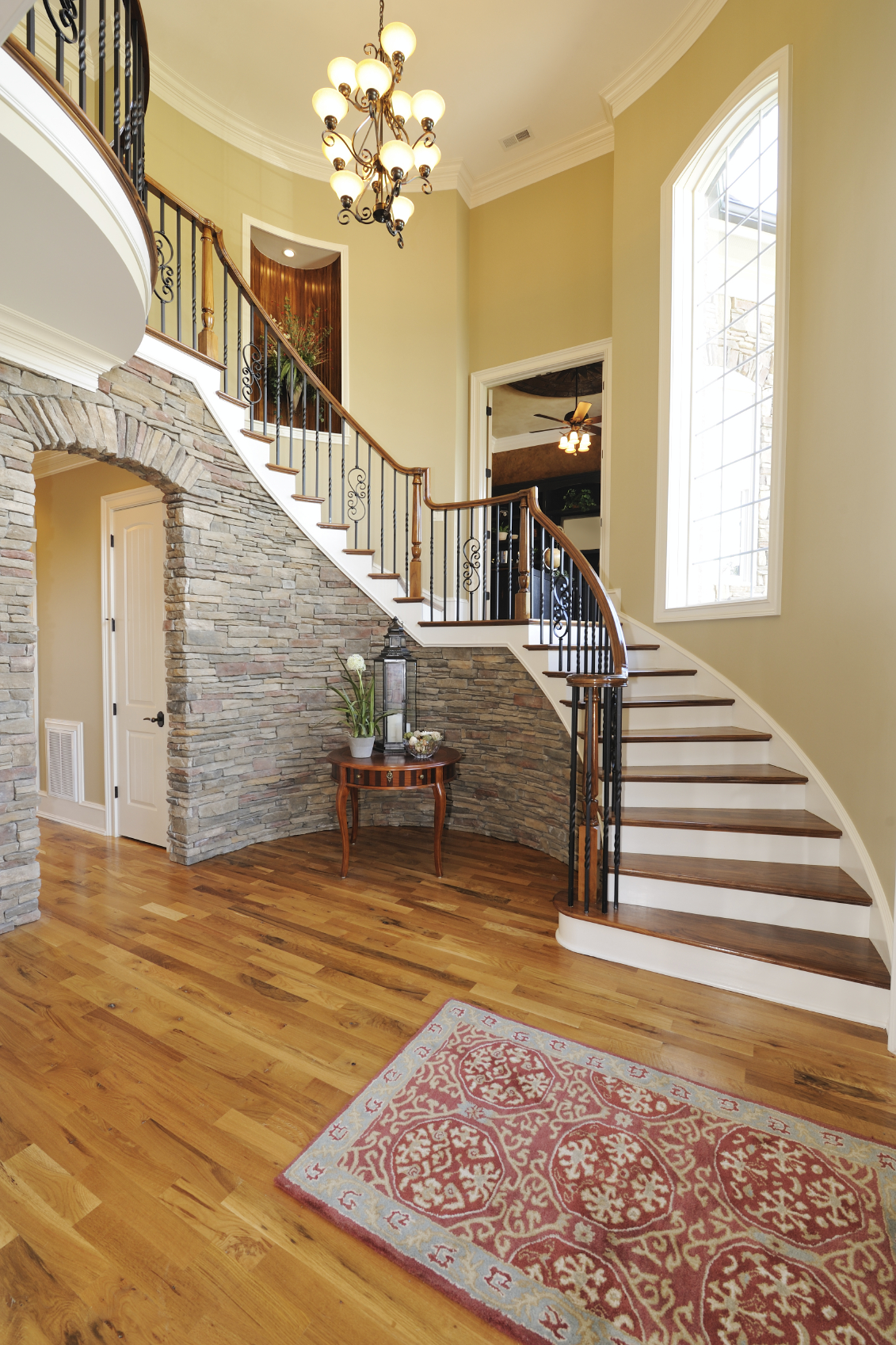 46-beautiful-entrance-hall-designs-and-ideas-pictures-the-spiral-staircase-sweeps-down-over-a-faux-stone-wall-archway-into-rest_decorating-hallway-ideas_ideas_graphic-design-ideas-small-backyard-jewel