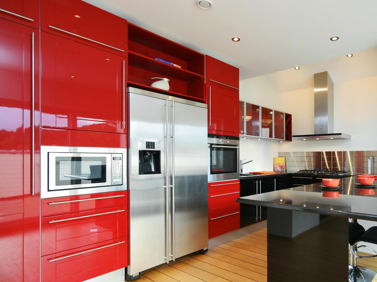 big-metal-refigerator-in-red-kitchen-cabinets-facing-black-countertop-on-wooden-floor
