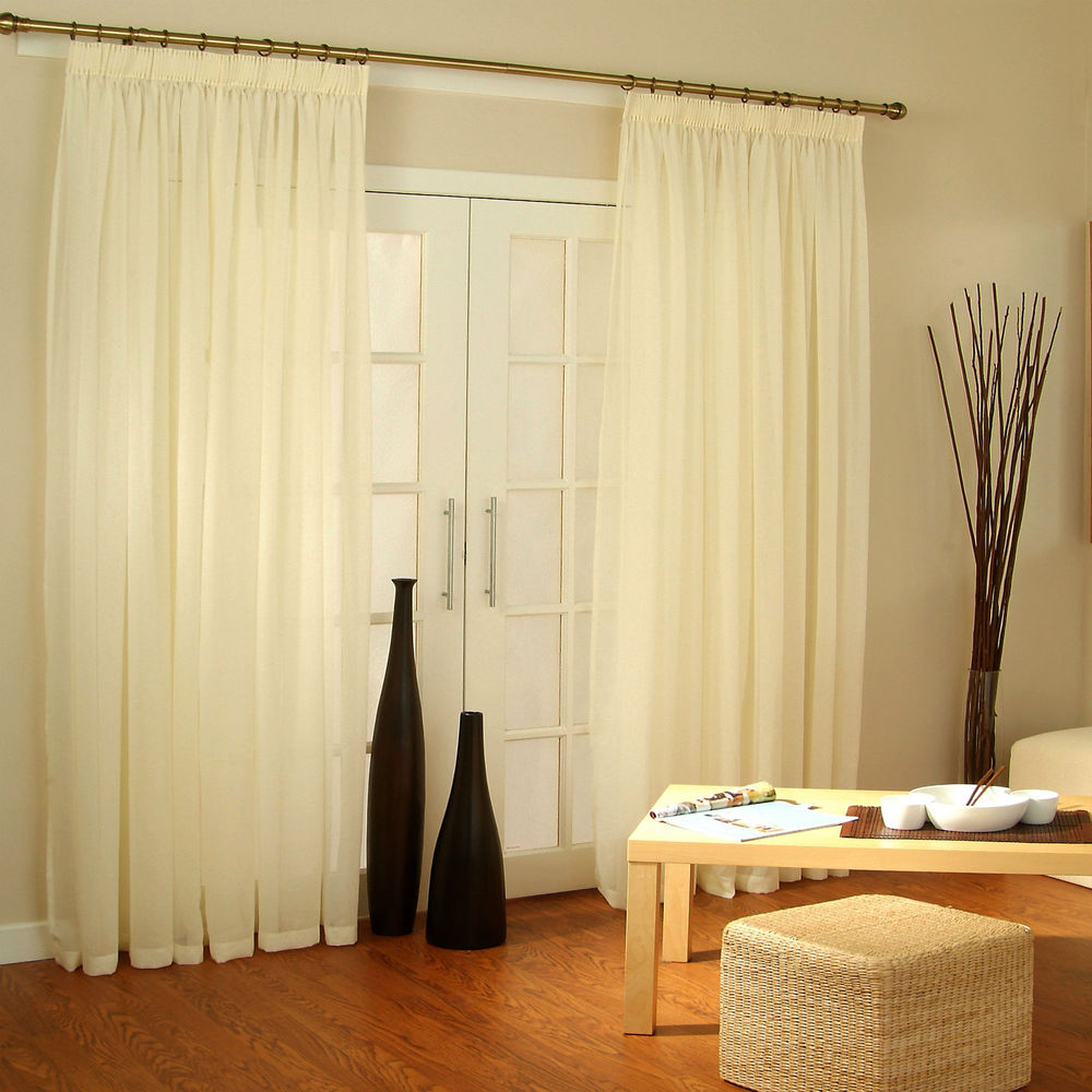 shiny-interior-living-space-with-wooden-table-and-rattan-ottoman-near-french-door-curtains