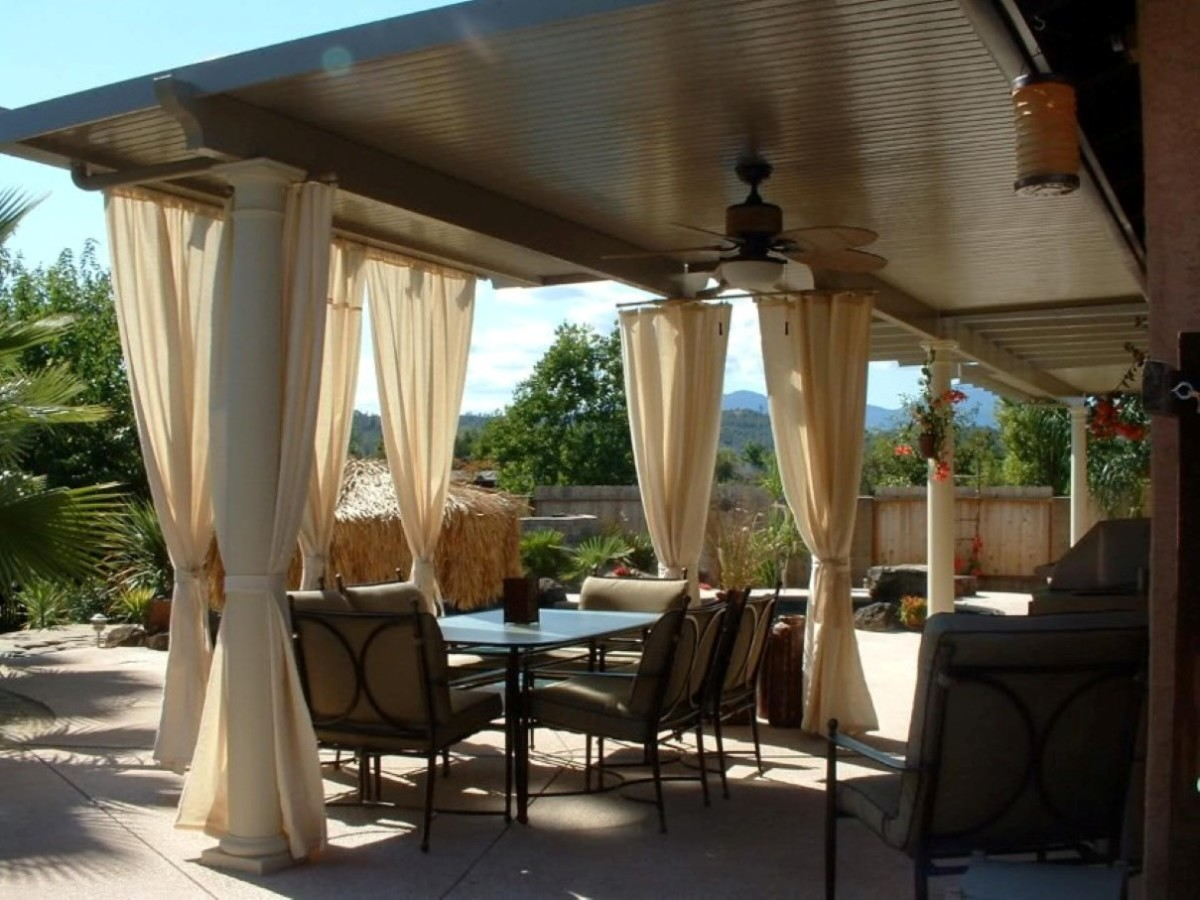 beautiful-beige-sheer-curtains-around-patio-with-tan-pads-on-black-iron-chairs-around-glass-dining-table-under-ceiling-fan-1200x900