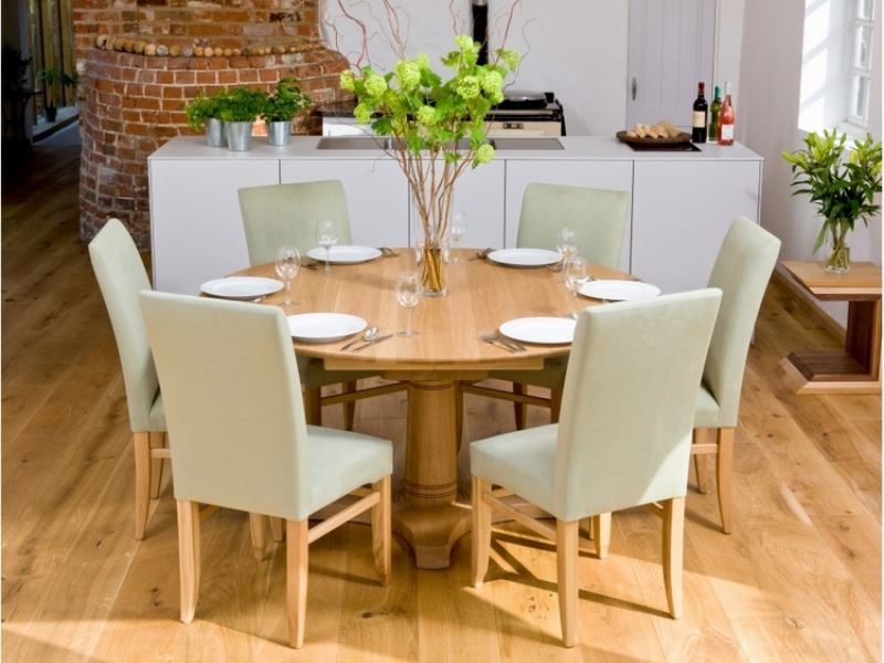 clean-round-wooden-dining-table-with-beige-upholstered-chairs-ikea-surrounding-set-in-front-of-white-kitchen-island-design