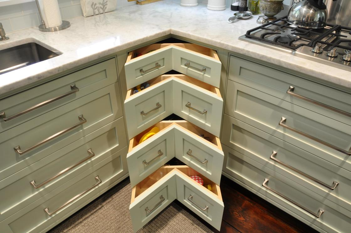 creative-design-interior-of-base-corner-kitchen-cabinet-in-antique-white-polished-wood-with-elbow-shaped-unique-drawers-using-long-stainless-steel-pull-handles-1120x743
