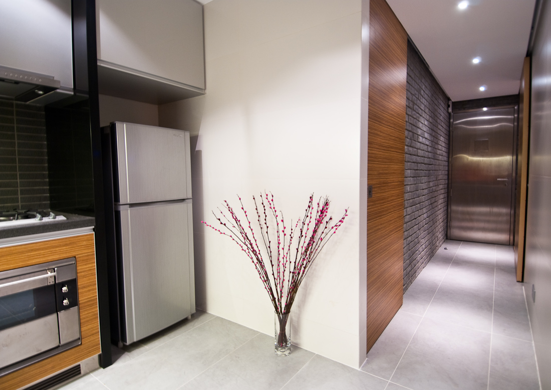 exterior-entrance-hall-with-a-kitchen-design-wall-decor-white-ceramic-gray-floor-fitted-wooden-wall-cabinets-lands-refrigerator-and-stove-oven-doors-and-wall-lights-flower-pots-beautiful-hallway-desig