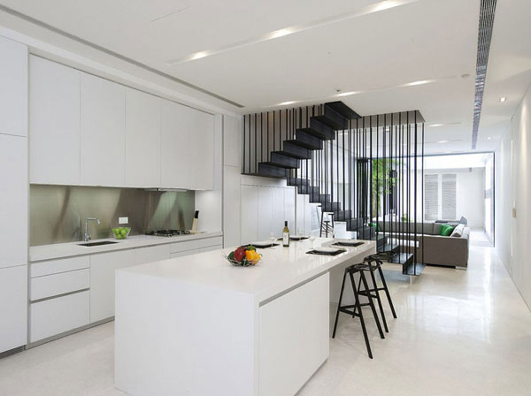 minimalist-design-of-apartment-kicthen-set-with-black-modern-bar-stools-beside-the-living-room-space