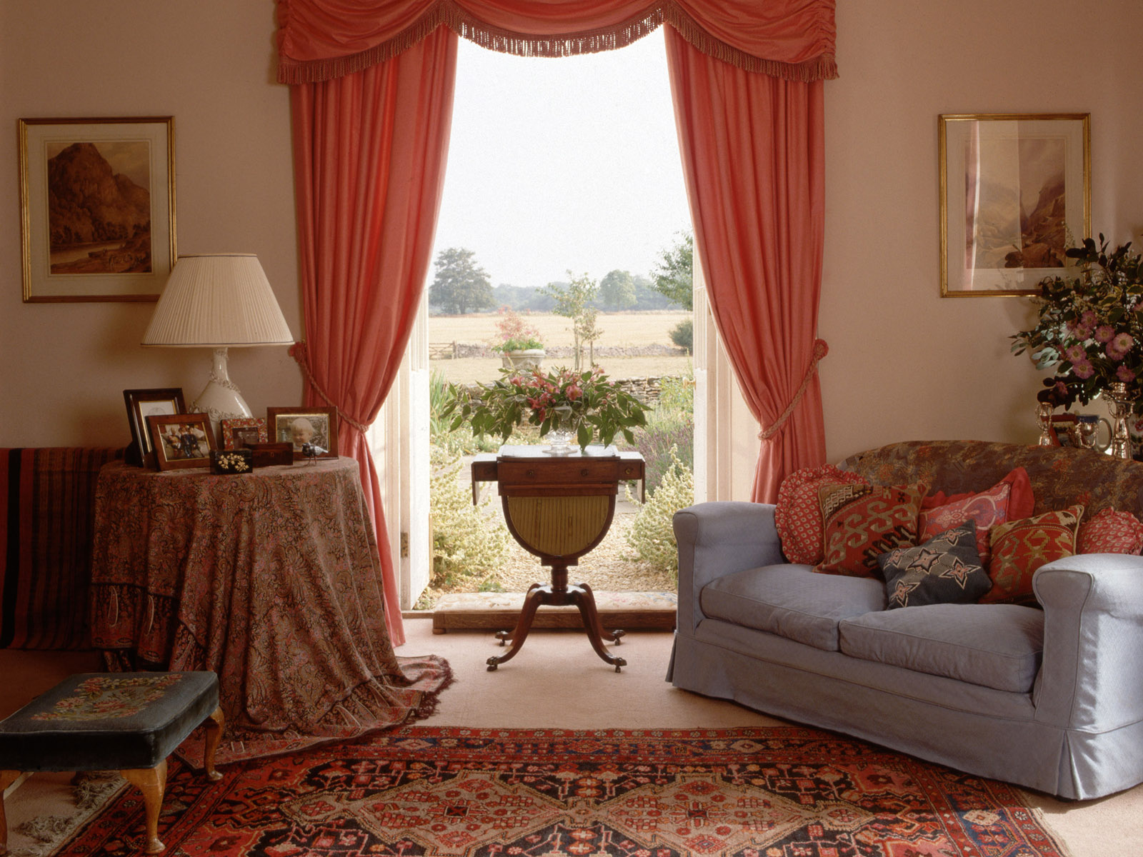 Red curtains frame a window in a country style living room.