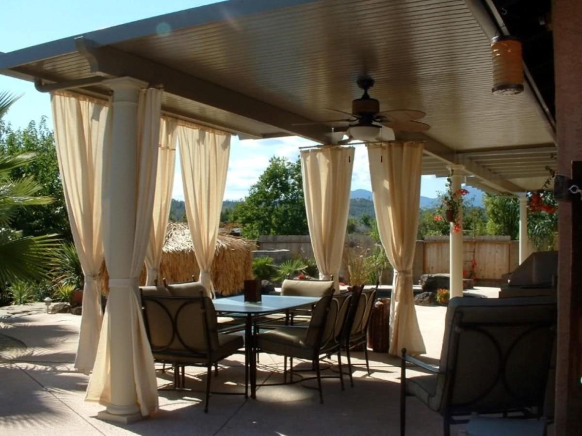 güzel-bej-şeffaf-perdeler-etrafında-veranda-ile-tan-pedleri-üzerinde-siyah-demir-sandalyeler-etrafında-cam-yemek-masası-tavan-fan-1200x900